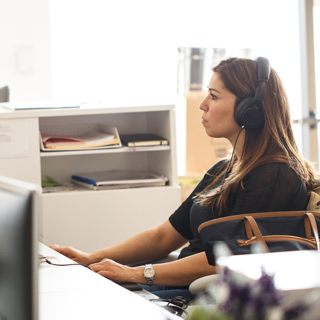 Woman wearing a headset seated in front of office computer.